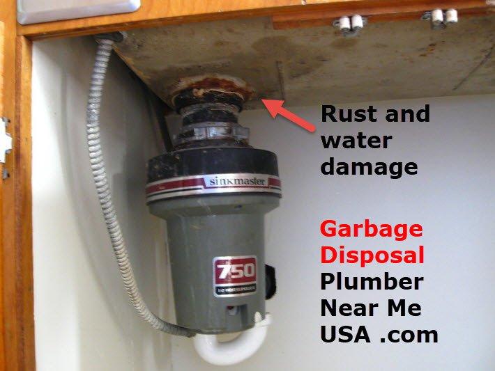 Rust and water damage around the garbage disposal. Garbage disposal Plumber Near Me USA .com