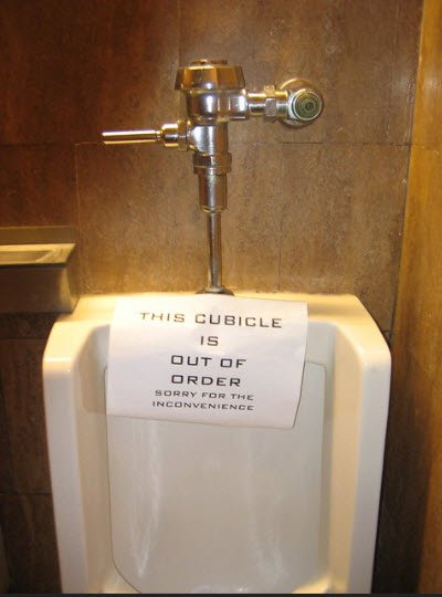 Leaking urinal with a sign that says: This cubicle out of order.