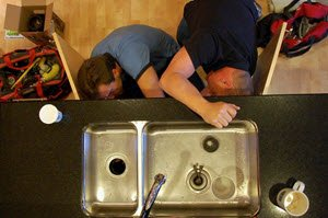 Two plumbers installing a garbage disposal. Plumber Near Me USA .com