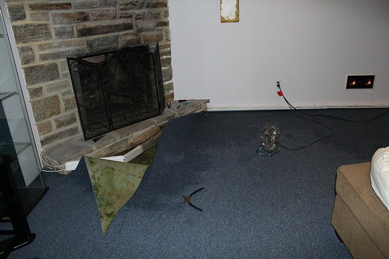 Wet carpet in basement near the fireplace.