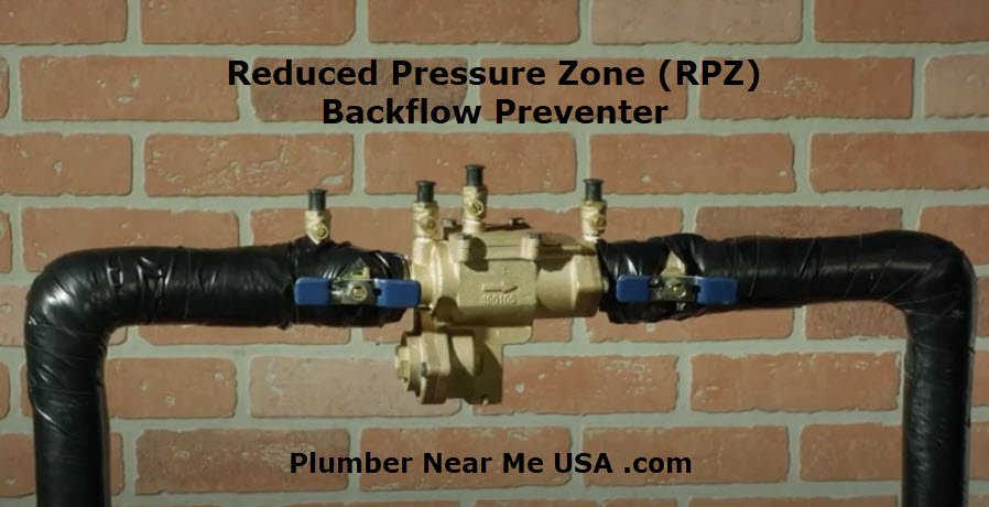 Reduced Pressure Zone (RPZ) Backflow Preventer installed on the outside of a brick house. Plumber Near Me USA .com