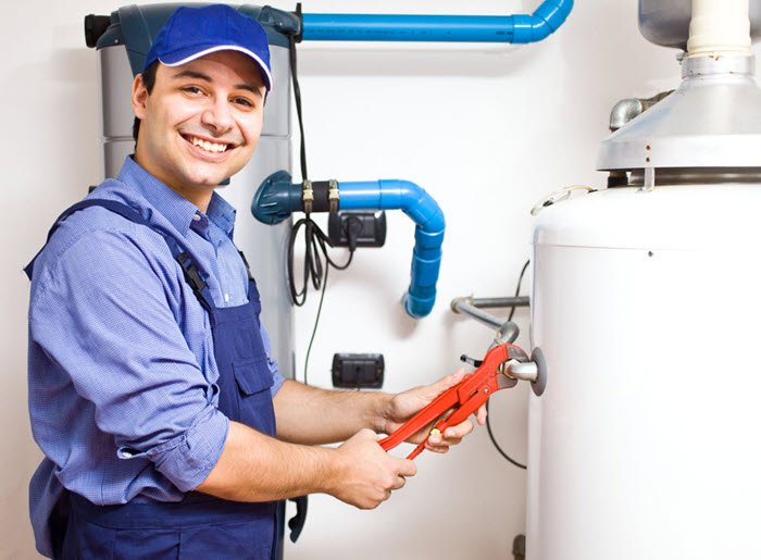 Smiling plumber installing a water heater.