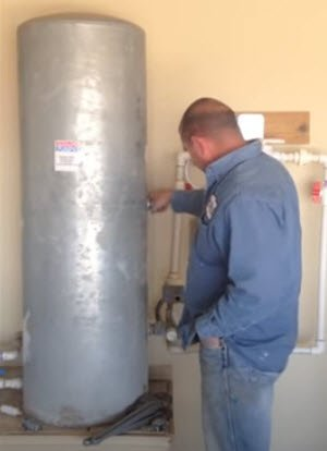 """Water well pressure tank being inspected by a local """"well plumber near me"""" expert."""